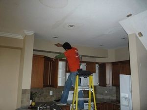 Technician Repairing Water Damage On Apartment Complex Ceiling